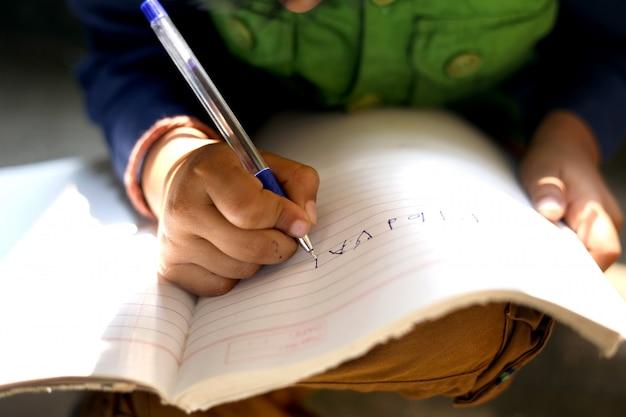 Criança indiana, escrevendo no caderno