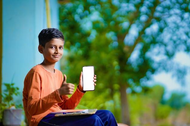 Criança indiana estudando em casa e mostrando a tela do smartphone.