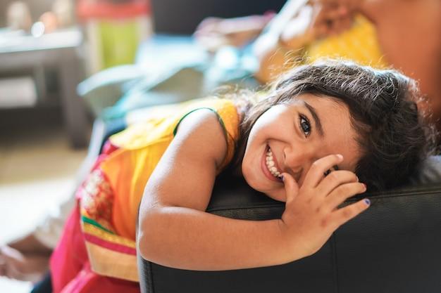 Criança indiana feliz se divertindo sentado no sofá com os pais em casa