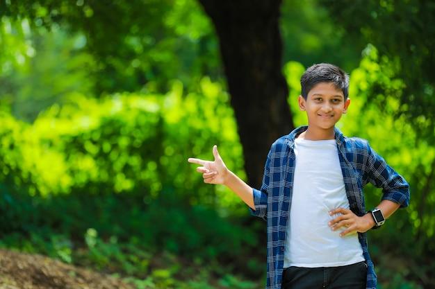 Criança indiana fofa mostrando a direção com a mão
