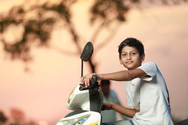Criança indiana fofa sentada na scooter e dando expressão múltipla
