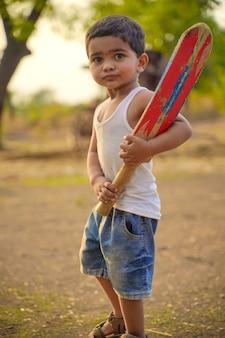 Criança indiana jogando críquete