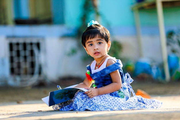Criança indiana pequena da menina que escreve no livro de nota, estudando