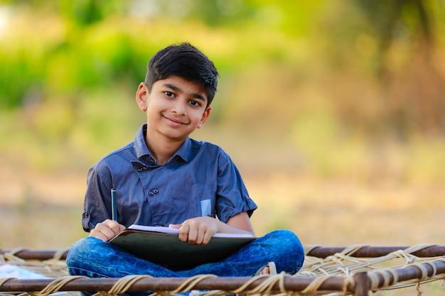 Criança indiana rural fazendo sua lição de casa na escola