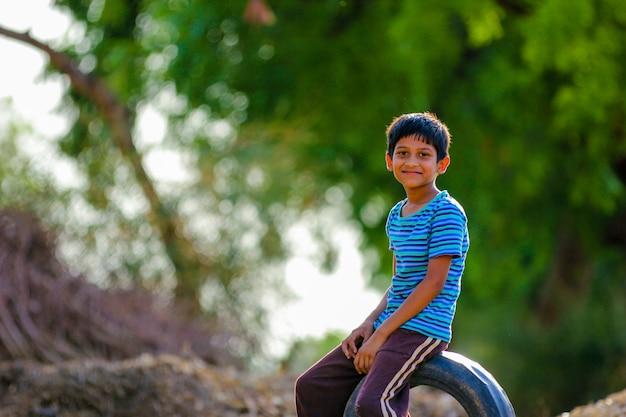 Criança indiana rural jogando críquete no chão