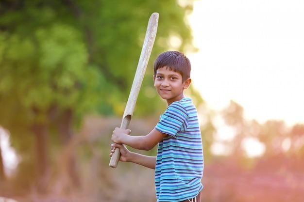 Criança indiana rural jogando críquete