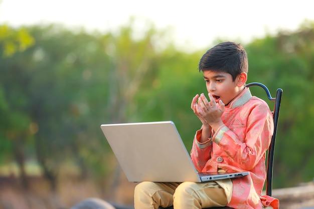 Criança indiana surpreendendo com boas notícias no laptop