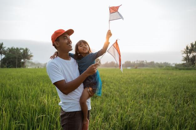 Criança indonésia com pai jogar com bandeira nacional