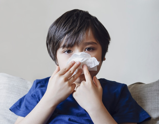Criança insalubre soprando nariz em tecido, criança que sofre de coriza ou espirros, um garoto pega um resfriado quando a estação muda, infância limpando o nariz com tecido
