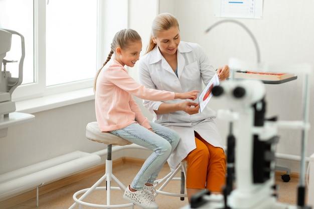Criança inteligente interessada pedindo apoio à linda médica