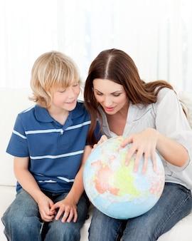 Criança interessada que olha um globo terrestre com sua mãe