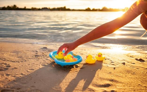 Criança irreconhecível brincando com patos de borracha na praia.