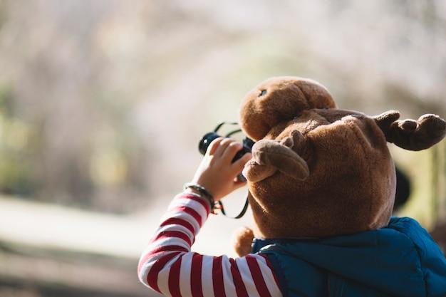 Criança irreconhecível usando binóculos