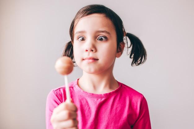 Criança isolada sobre a parede. segure o pirulito colorido na mão e olhe para ele. pirulito saboroso e açucarado. garota séria e concentrada.