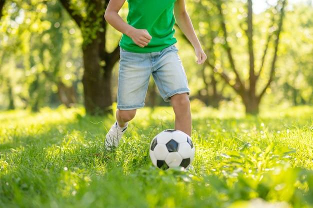 Criança jogando futebol no gramado verde