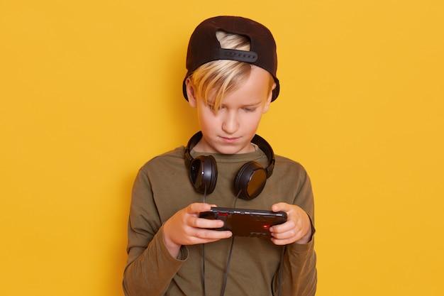 Criança jogando jogos online, menino com dispositivo digital, criança do sexo masculino veste camisa verde e boné com fones de ouvido