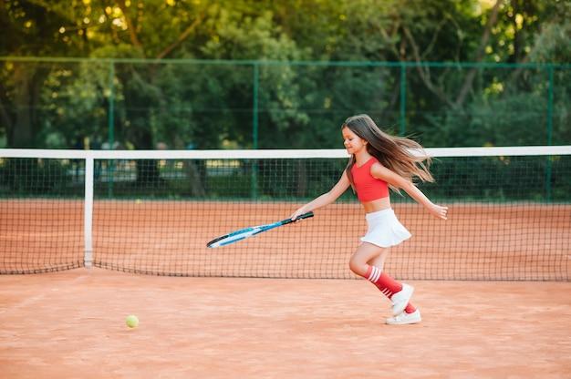 Criança jogando tênis na quadra ao ar livre. menina com raquete de tênis e bola no clube de esporte. exercício ativo para crianças