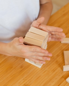 Criança jogando um jogo de torre de madeira em casa