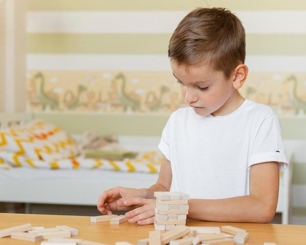 Criança jogando um jogo de torre de madeira sozinha