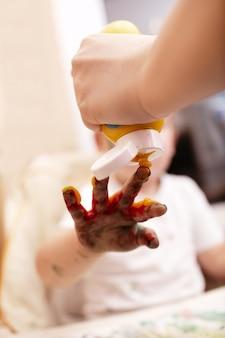 Criança jovem, tocando, com, dedo, pintura