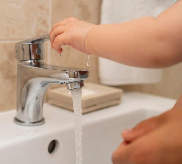 Criança lavando as mãos com ajuda dos pais