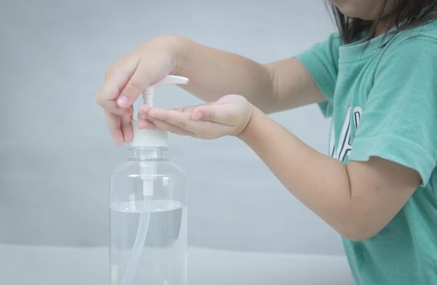 Criança lavando as mãos com gel de álcool