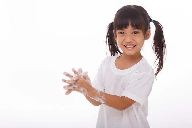 Criança lavando as mãos e mostrando as palmas das mãos com sabão