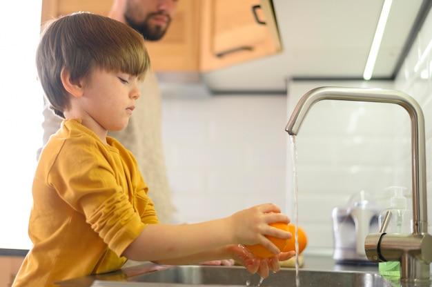 Criança lavando um limão na pia