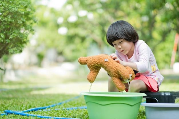Criança lavar boneca, criança feliz