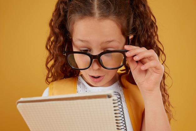 Criança lendo atentamente as anotações dela