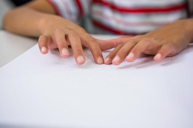 Criança lendo livro braille em sala de aula
