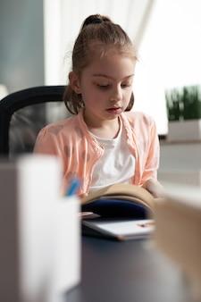 Criança lendo livro escolar para o prazo final dos trabalhos de casa