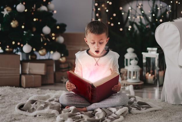 Criança lendo um livro encantado