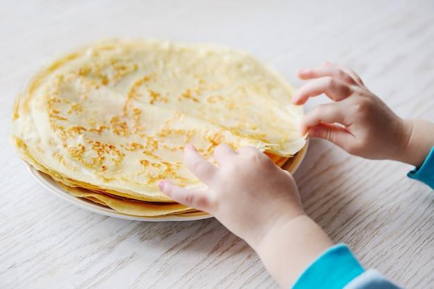 Criança leva uma panqueca de um prato com panquecas