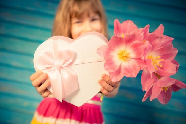 Criança linda com buquê de flores primavera conceito férias em família dia das mães