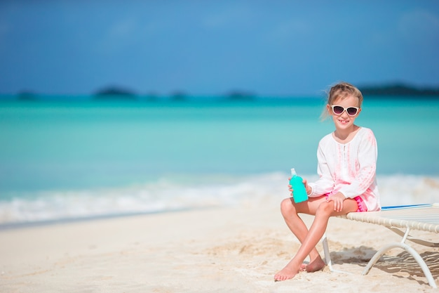 Criança linda com garrafa de protetor solar na praia tropical