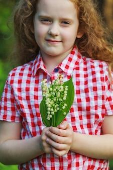 Criança linda com lírio do vale na floresta de primavera.