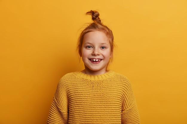 Criança linda e alegre com cabelo ruivo natural, sorri positivamente, parece com humor positivo, usa um suéter amarelo de tricô, nota algo incrível e atraente, sorri com os dentes