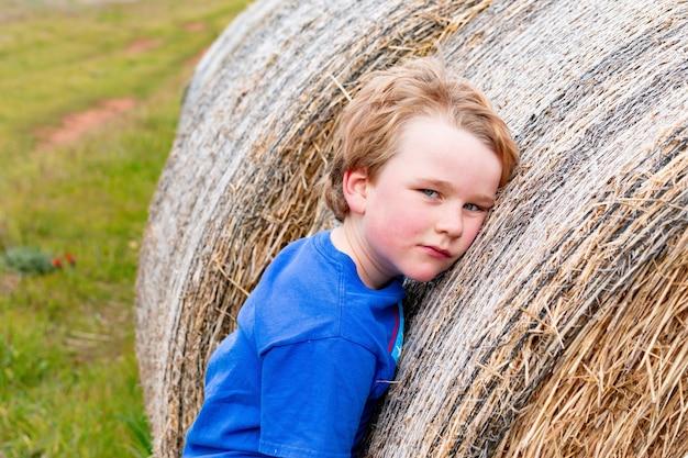 Criança loira apoiada em uma longa fileira de fardos de feno redondos em um dia nublado