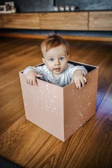 Criança loira bonita e curiosa, caucasiana, com lindos olhos azuis, sentada em uma caixa