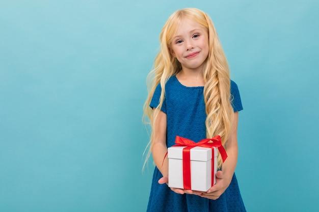 Criança loira bonita em um vestido com um presente nas mãos, sobre um fundo azul claro