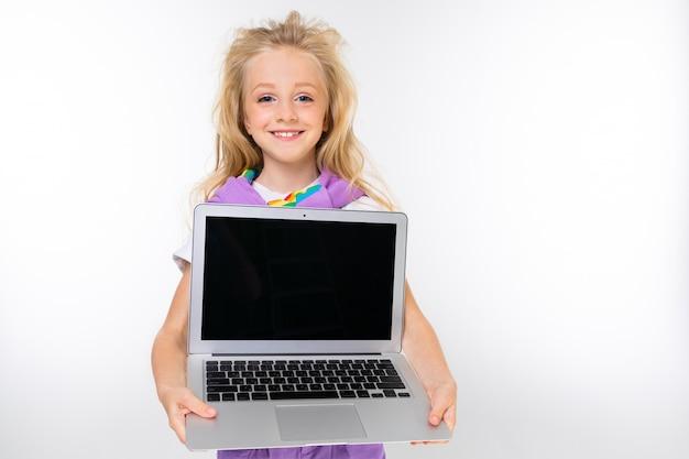 Criança loira com um visual casual mostra uma tela de laptop com uma maquete em uma parede branca