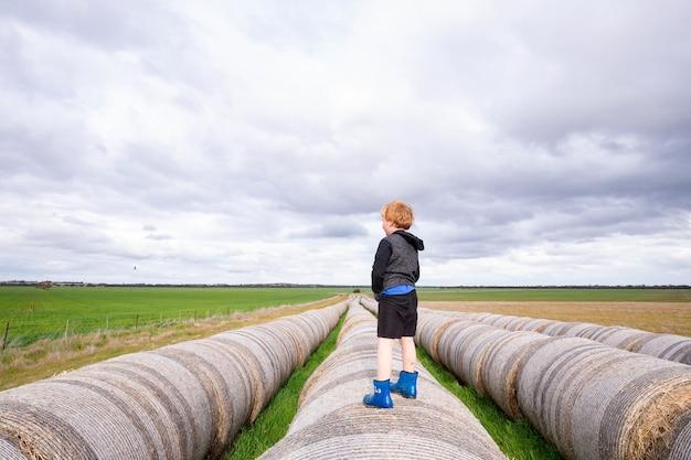 Criança loira em pé sobre uma longa fileira de fardos de feno redondos em dia nublado - infância na fazenda