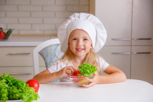 Criança loira no chapéu de um chef na cozinha comendo legumes