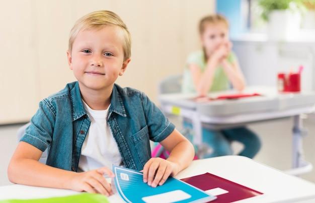Criança loira sentada em sua mesa
