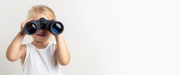 Criança loira sorridente olha através de binóculos sobre um fundo claro no estúdio. bandeira.