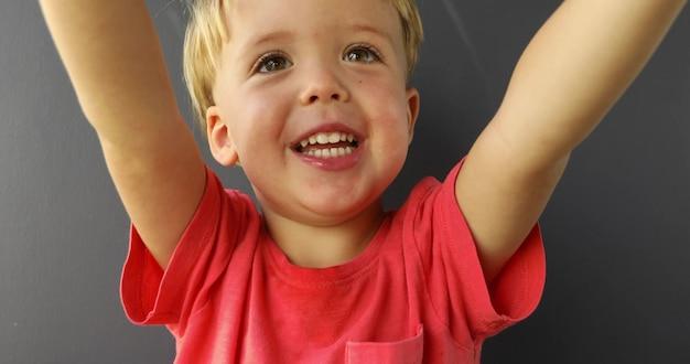 Criança loura bonita que sorri pedindo a preensão