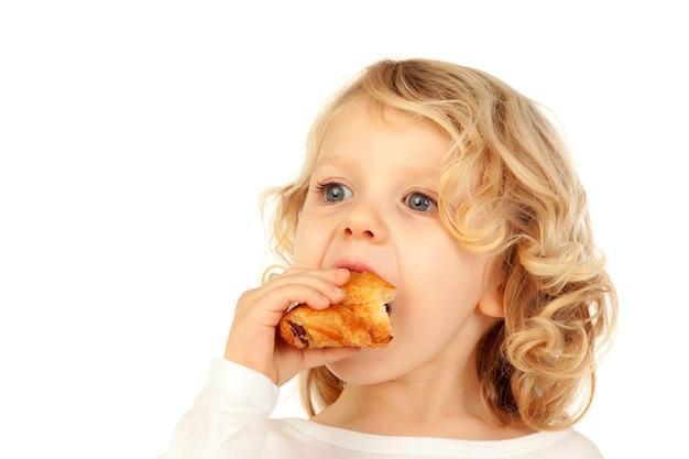 Criança loura pequena que come um croissant