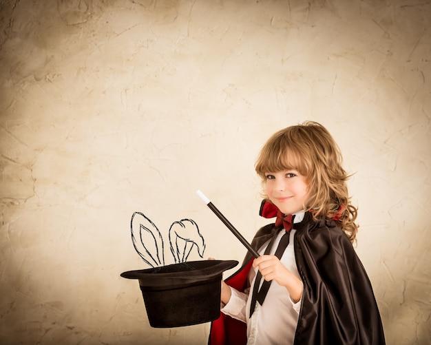 Criança mágica segurando uma cartola com um coelho desenhado contra um fundo grunge
