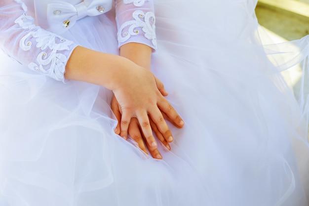Criança, mãos, vestido branco